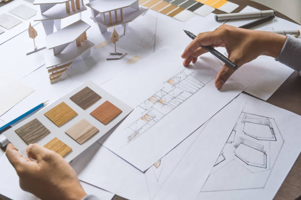 architect design working drawing sketch plans blueprints and making architectural construction model in architect studio stock photo