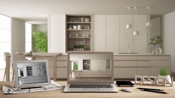 Architect designer desktop concept, laptop and tablet on wooden desk with screen showing interior design project and CAD sketch, blurred draft in the background, modern white kitchen stock photo