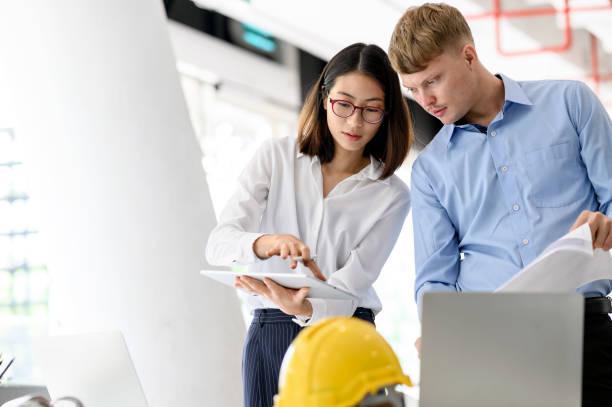 Colegas del equipo de ingenieros de diseño de arquitecto que trabajan con Blueprint y Tablet en la oficina. - foto de stock