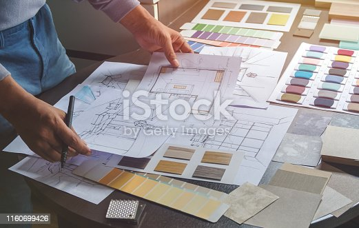 istock Architect designer Interior creative working hand drawing sketch plan blue print selection material color samples art tools Design Studio 1160699426