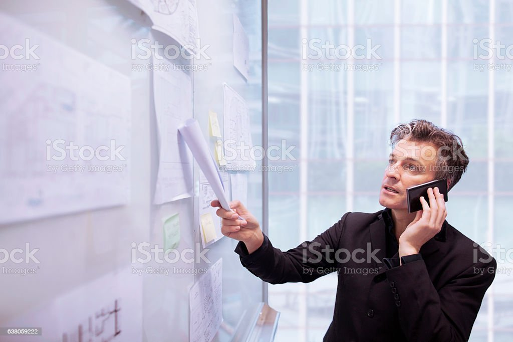 Architect designer using phone pointing to plans on wall stock photo
