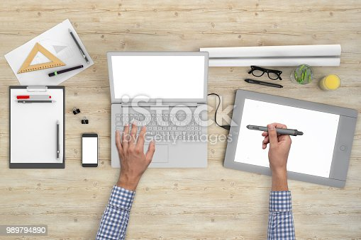 Man working on PC laptop. Office wooden desk knolling overhead concept, top close up with tablet, mobile phone, drawing pad, pencils, notebook and glasses.  blank screen template