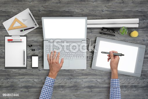 Architect designer working on PC laptop with drawing tablet. Office wooden desk knolling overhead concept, top close up with tablet, mobile phone, drawing pad, pencils, notebook and glasses.  blank screen template
