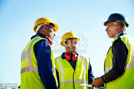 Low angle view of male architect discussing with quarry workers against clear sky