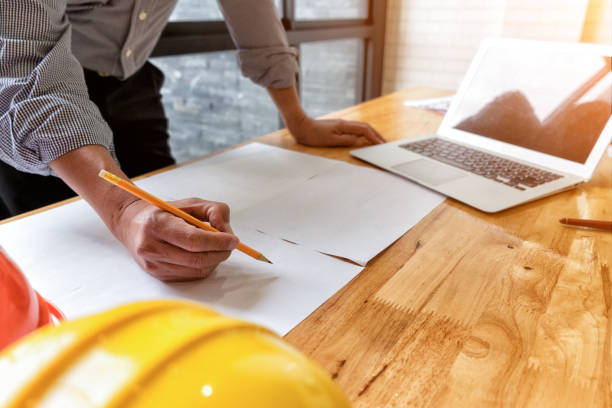 architect drawing architectural project on blueprint with laptop – Foto