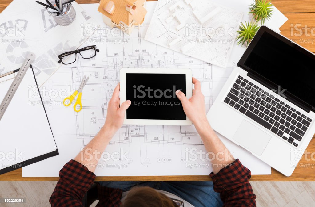 Architect drawing on architectural project on digital tablet. Top...