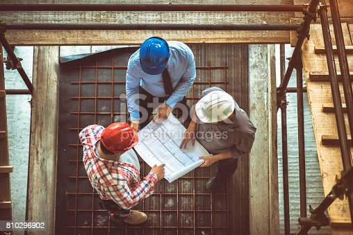 istock Architect, engeneer and foreman on a construction site 810296902