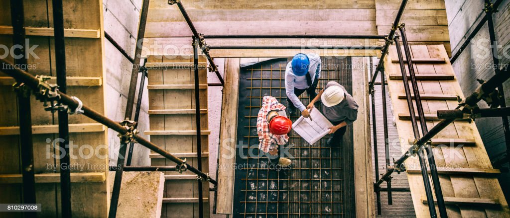 Architect, engeneer and foreman on a construction site stock photo