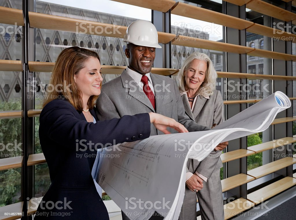 Architect Engineer and Client Look Over a Set of Prints stock photo