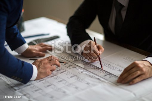 istock Architect, engineer and foreman discuss with blueprint in office 1126517442