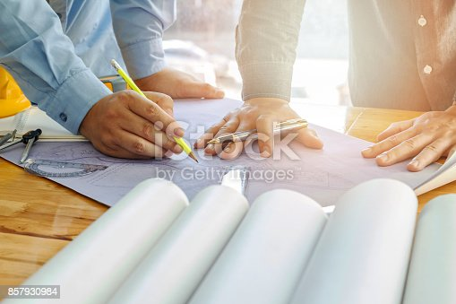 istock Architect, engineer and foreman discuss with blueprint in office 857930984