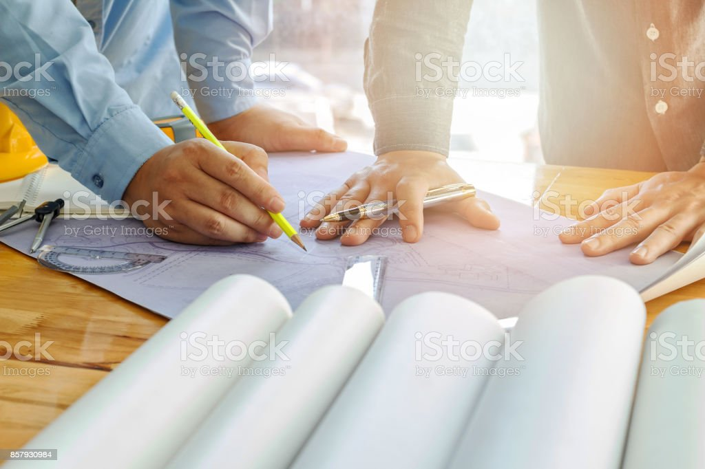 Architect, engineer and foreman discuss with blueprint in office stock photo