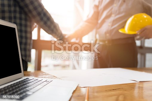 istock architect engineer shaking hands beside window - business 587518390