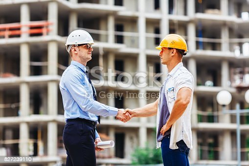 1055059750 istock photo Architect engineer shaking hands other hand at construction site.  Business teamwork, cooperation, success collaboration concep 827239110