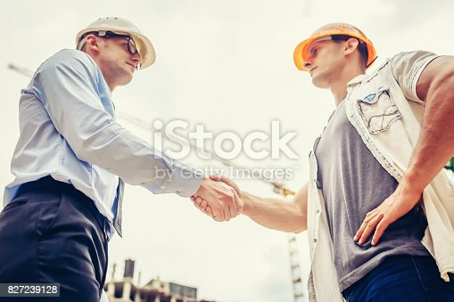1055059750 istock photo Architect engineer shaking hands other hand at construction site.  Business teamwork, cooperation, success collaboration concep 827239128