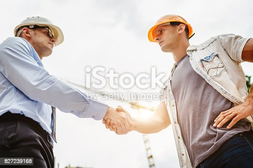 1055059750 istock photo Architect engineer shaking hands other hand at construction site.  Business teamwork, cooperation, success collaboration concep 827239168