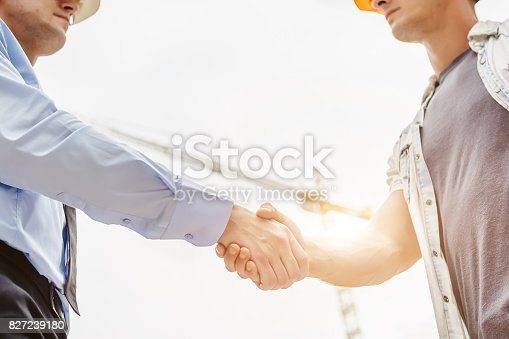 1055059750 istock photo Architect engineer shaking hands other hand at construction site.  Business teamwork, cooperation, success collaboration concep 827239180