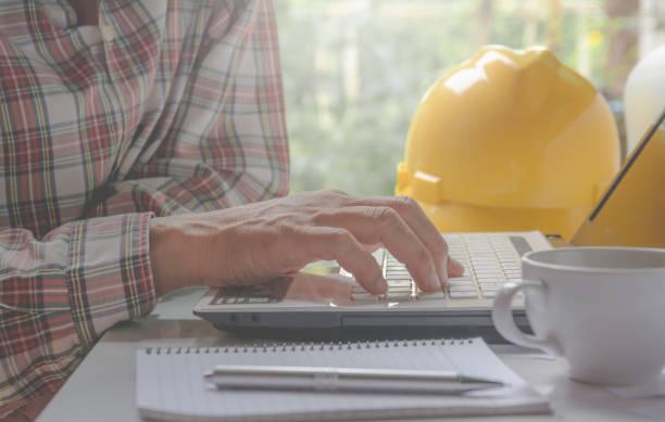 Architekt Ingenieur mit Laptop für die Arbeit mit gelben Helm, Laptop und Kaffeetasse auf dem Tisch. – Foto