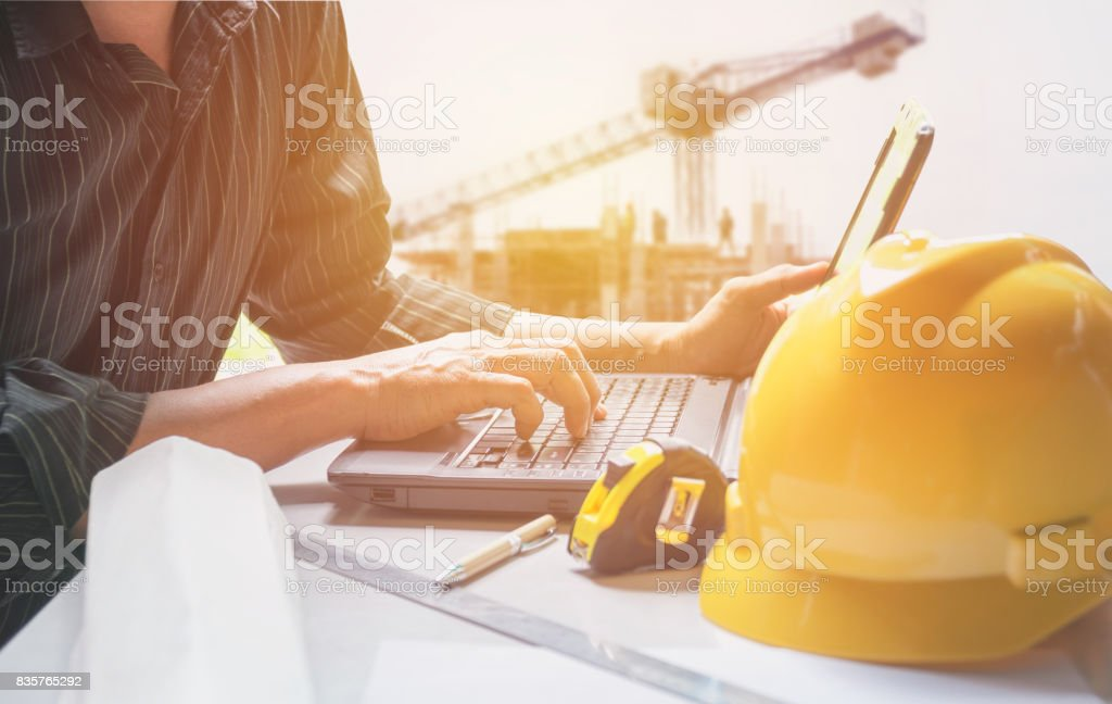 Architect engineer using laptop for working with yellow helmet, laptop and coffee cup on table. stock photo