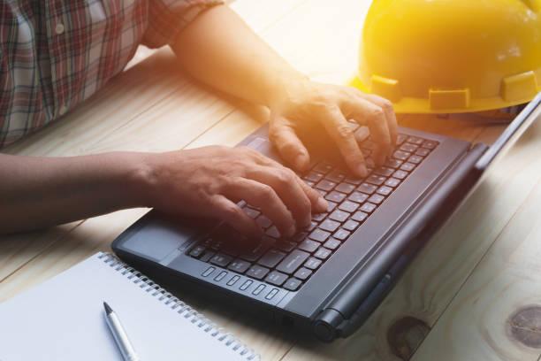 Architekt Ingenieur mit Laptop für die Arbeit mit gelben Helm auf Tisch. – Foto