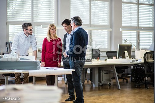 istock Architect explaining architectural model to couple 480342310
