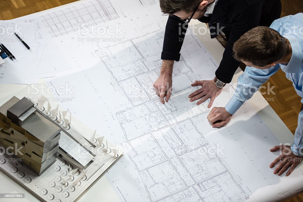 Architect explaining blueprint to client stock photo