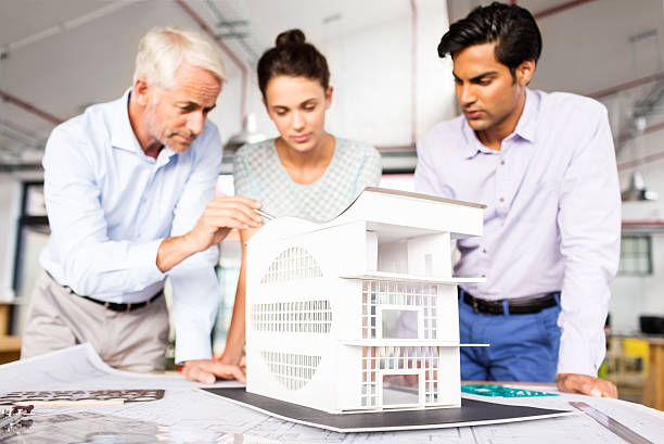 Architect Explaining House Model To Colleagues At Office Desk stock photo