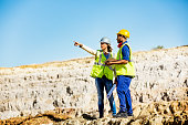 Female architect explaining plan to quarry worker at construction site against clear sky