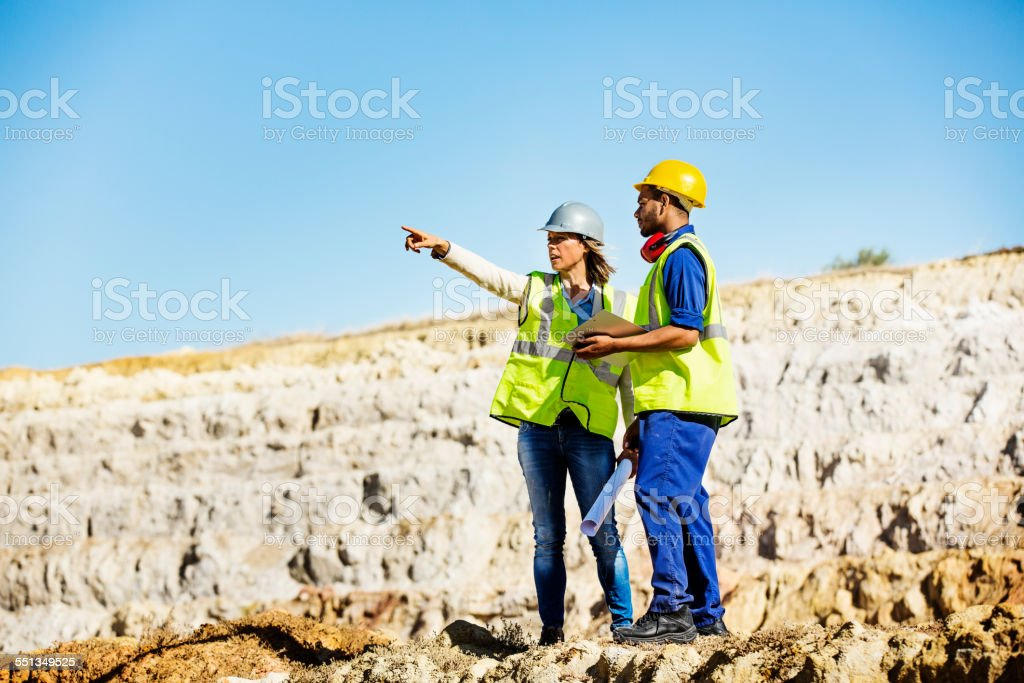 Architect explaining plan to quarry worker at site stock photo