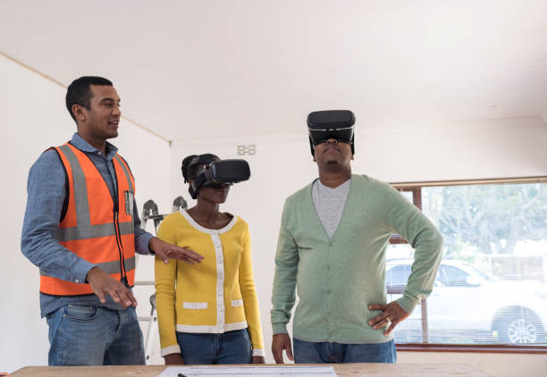 Architect explaining renovation plans to couple while they are wearing VR glasses stock photo