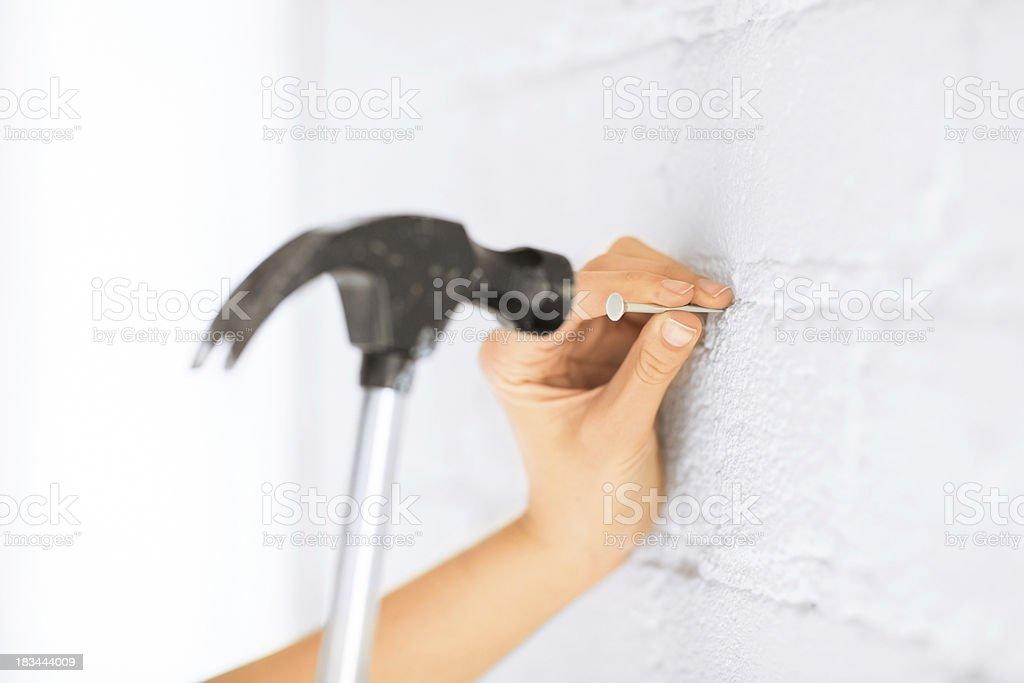 architect hammering nail in wall royalty-free stock photo
