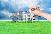 architect hand drawing a house on the grass field and sky background