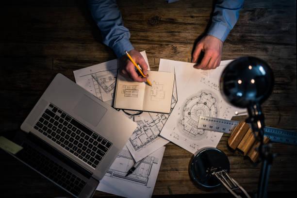 architekt handzeichnung an seinem schreibtisch - bürolampe stock-fotos und bilder