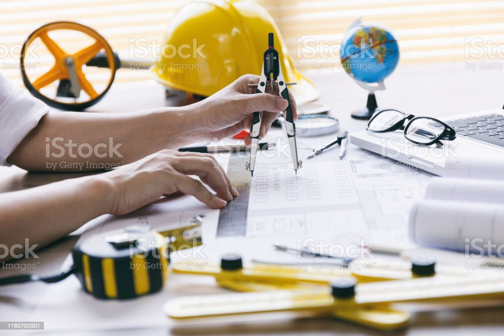 Architect hands working on blueprint plans with a pencil, a ruler,...
