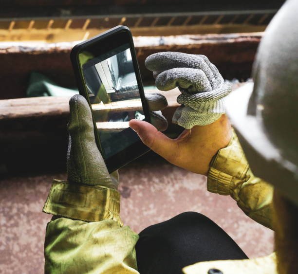 Architect holding a smartphone on construction site. young construction worker is using mobile phone on site. Construction worker with building plans and cellphone. Focus on mobile. warm vivid filter. Top view of two construction workers wearing hardhats stock photo