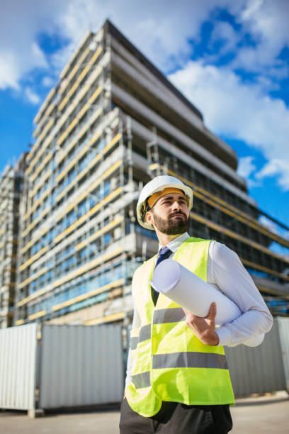 Architect holding blueprints and looking away stock photo