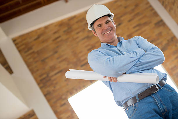 architect holding blueprints at a construction site - civil engineer stock photos and pictures