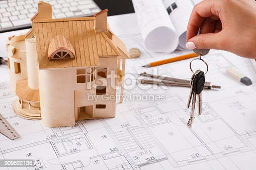 istock Architect holding keys at house model in office 909522138