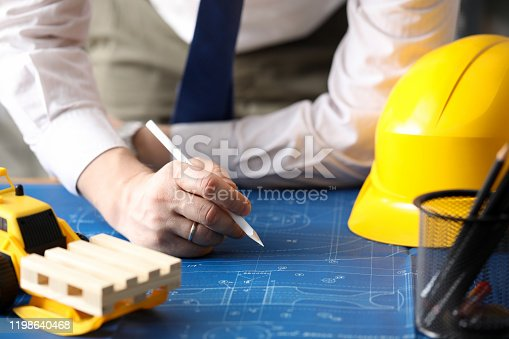 Close-up of male hand of builder painting drawing at workplace. Toy yellow bulldozer and helmet on blueprint at desktop. Construction and business concept