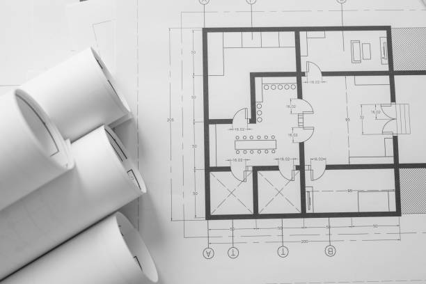Architect house plan roled -up plans on the table, high angle view. stock photo