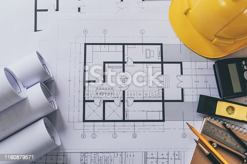 1174841541 istock photo Architect house plan roled -up plans on the table, high angle view. 1160879571