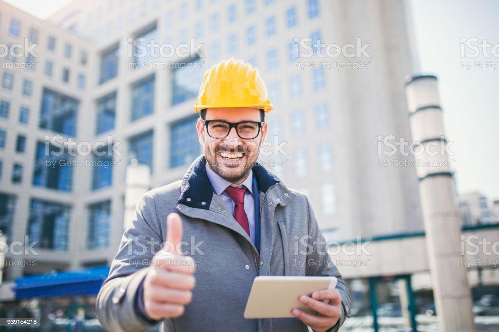 Arquitecto en dedo pulgar mostrando de casco protector para arriba frente a edificio de oficinas - foto de stock
