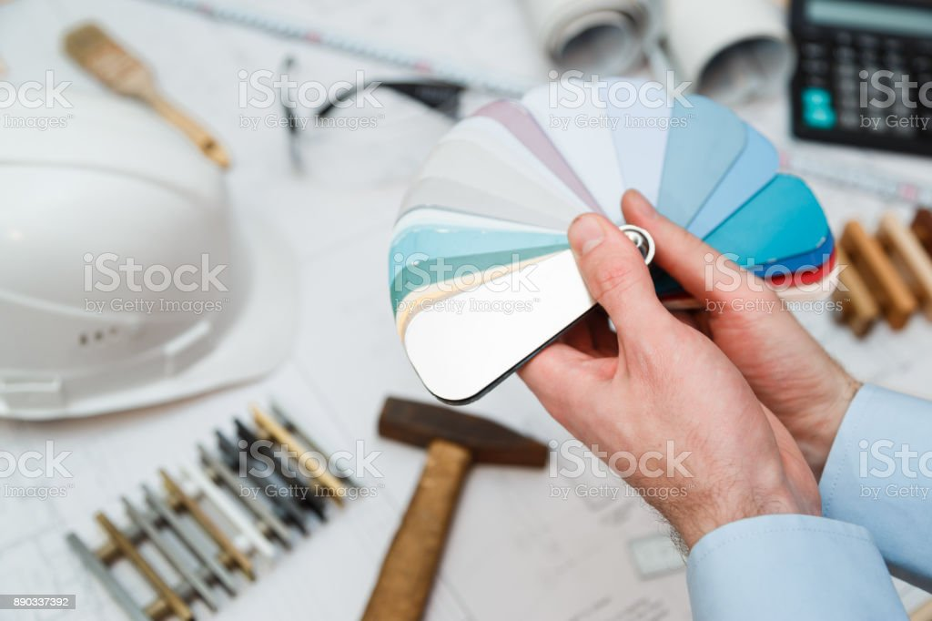 Architect interior's hands drawing home illustration with material sample, renovation concept. stock photo