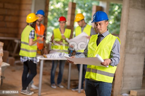 516607254istockphoto Architect look at blue print 516605644