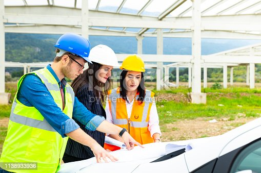 Architect looking at blueprints on construction site