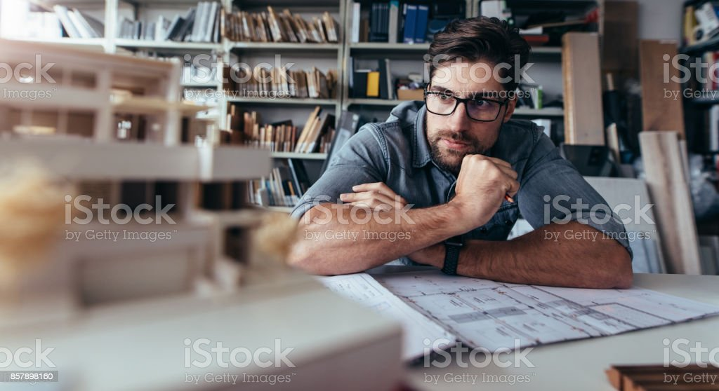 Architect looking at house model on desk stock photo