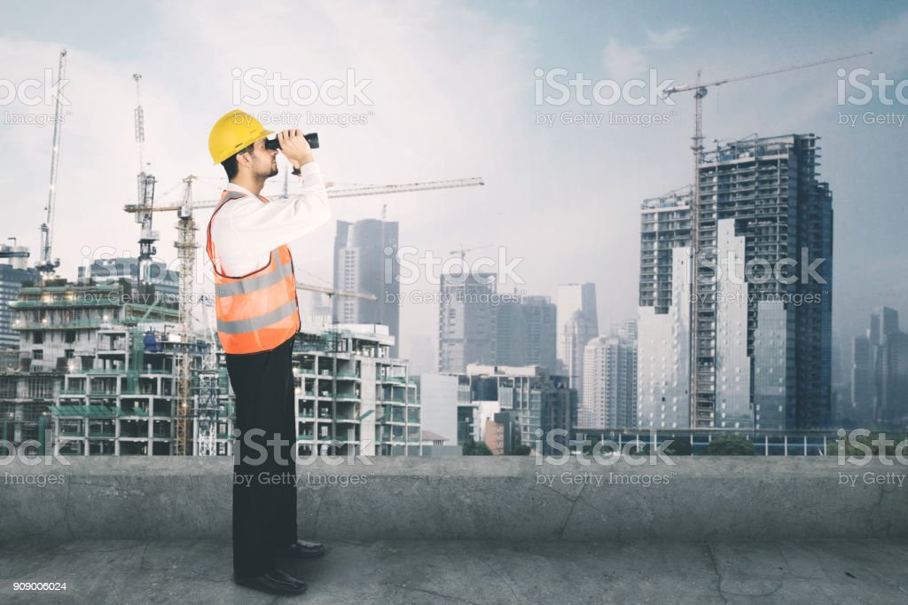 Architect looking at the construction site with binocular stock photo