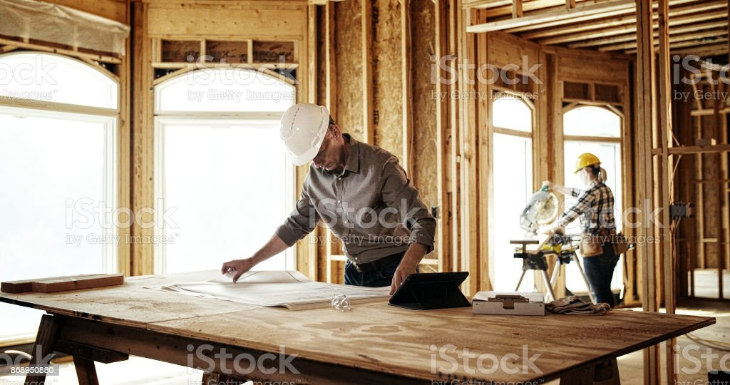 Architect looking over blueprints stock photo
