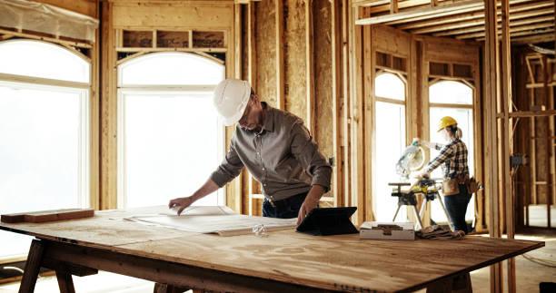 Architect looking over blueprints stock photo
