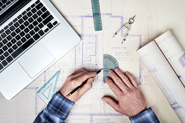 Architect making floor plans using computer and graph tools stock photo